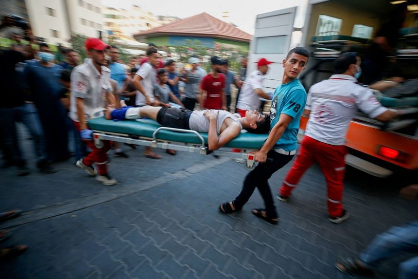 A wounded Palestinian is carried on a stretcher after taking part in a protest at the Israel-Gaza border.