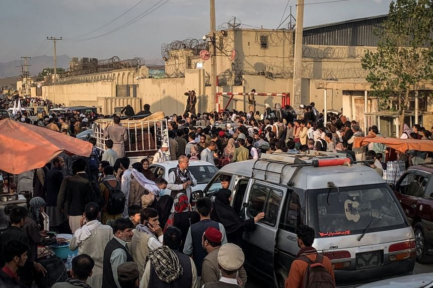 Hoping to flee the country, people gather near the airport in Kabul, on Aug. 21, 2021.