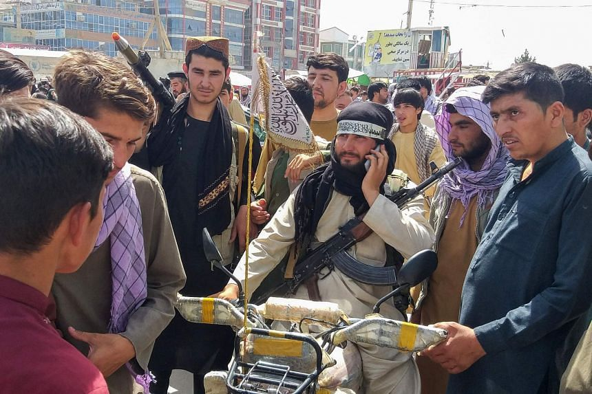 A Taleban fighter (centre) is seen surrounded by locals in Pul-e-Khumri, the capital of Baghlan province, on Aug 11, 2021, after it was captured by the Taleban.
