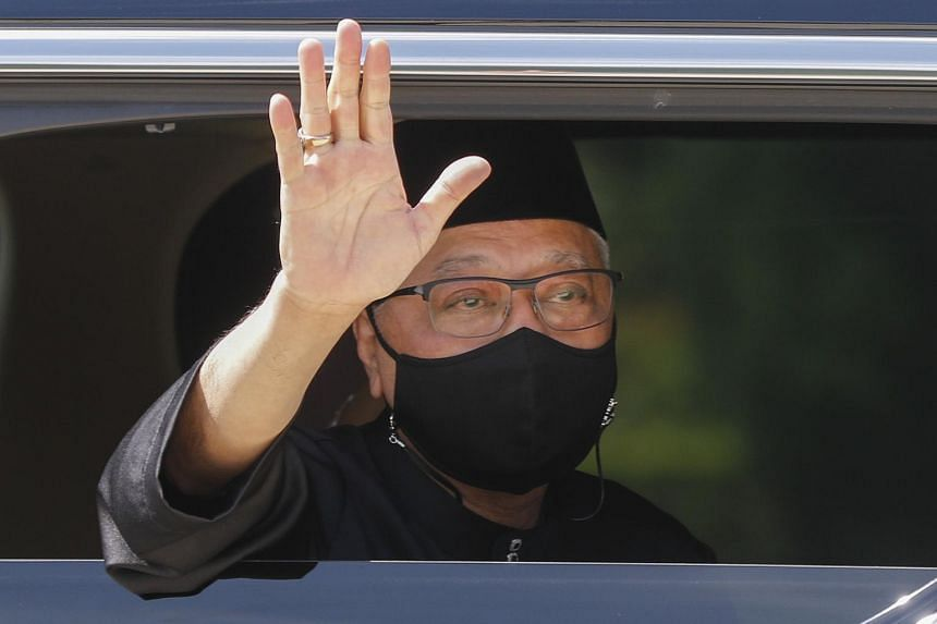 Malaysian Prime Minister Ismail Sabri Yaakob waves from a vehicle as he leaves the National Palace after the swearing in ceremony in Kuala Lumpur on Aug 21, 2021.