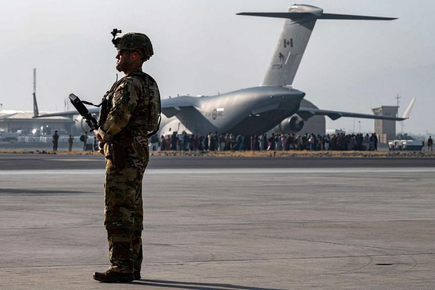 A member of the US Air Force security force standing guard near a US Air Force C-17 Globemaster III aircraft in Kabul's airport on Aug 20, 2021.