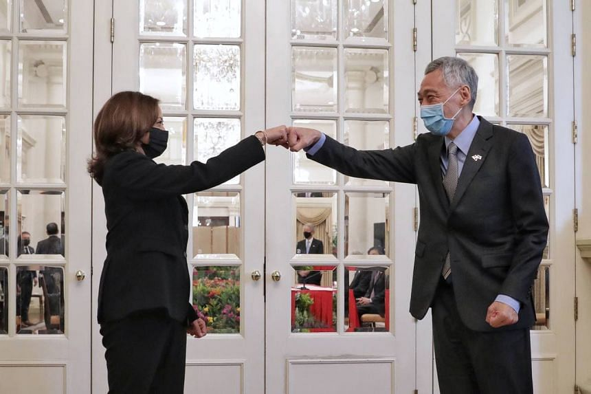 Prime Minister Lee Hsien Loong fist-bumps US vice-president Kamala Harris before a delegation meeting at the Istana on Aug 23, 2021.