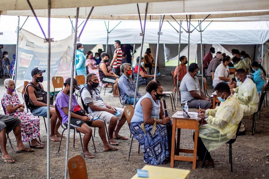 People wait in queue for their first dose of the AstraZeneca Covid-19 vaccine in Suva, Fiji on Aug 9, 2021.