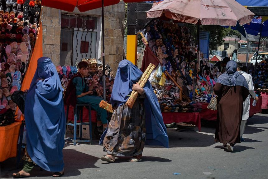 Burqa-clad women shopping at a market area in Kabul on Aug 23, 2021, following the Taliban's military takeover of the country.