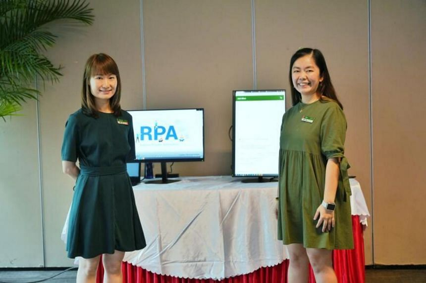 Ms Chiew Bee Lian (left) and Ms Kelly Lim showing the chatbot MICO and Robotic Process Automation for birthday greetings.