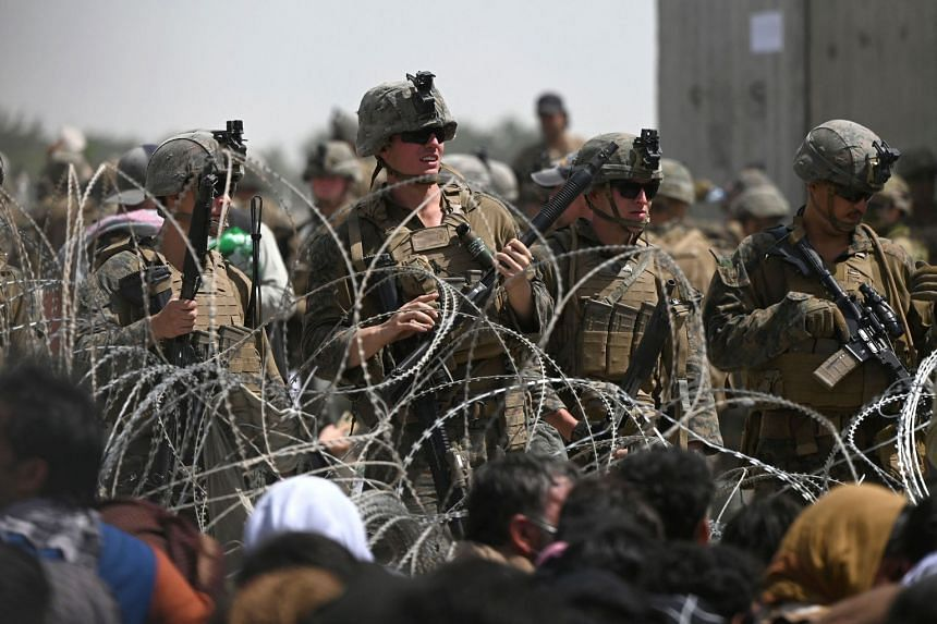 US soldiers stand guard behind barbed wire as Afghans sit on a roadside near the military part of the airport in Kabul on Aug 20, 2021.