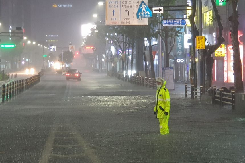 A police officer directs traffic on a submerged road in the port city of Busan, on Aug 24, 2021.