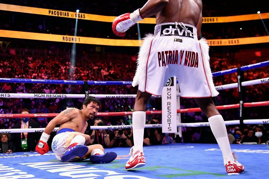 Manny Pacquiao (left) looks at Yordenis Ugas of Cuba after a slip during their WBA Welterweight Championship boxing match in Las Vegas.