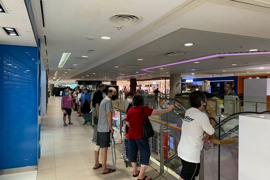 People queue for their free masks at Junction 8 mall on Aug 26, 2021.