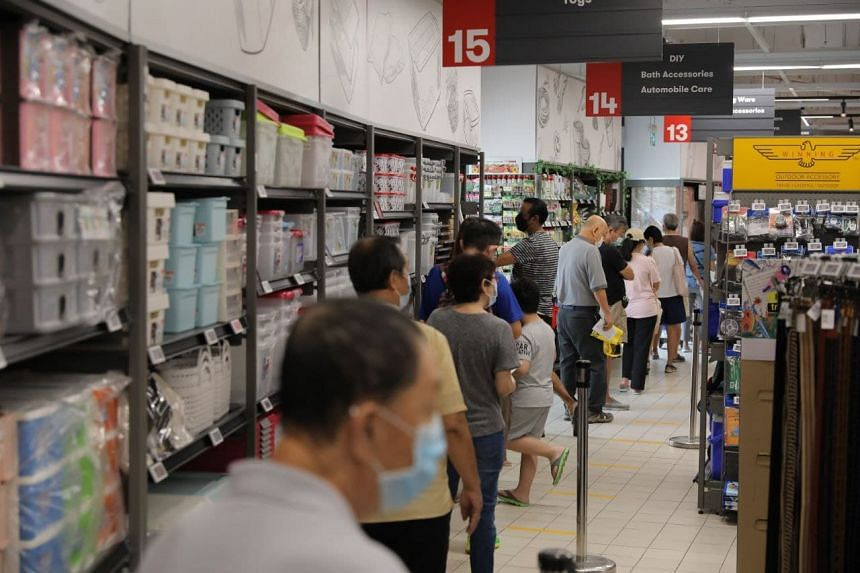 People queue to collect masks at FairPrice Xtra at Hougang 1 on Aug 26, 2021.