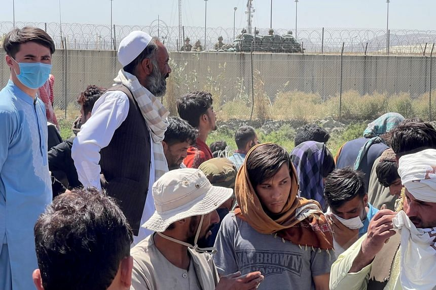 People line up as they prepare to show their documents to US troops outside the airport in Kabul on Aug 26, 2021.