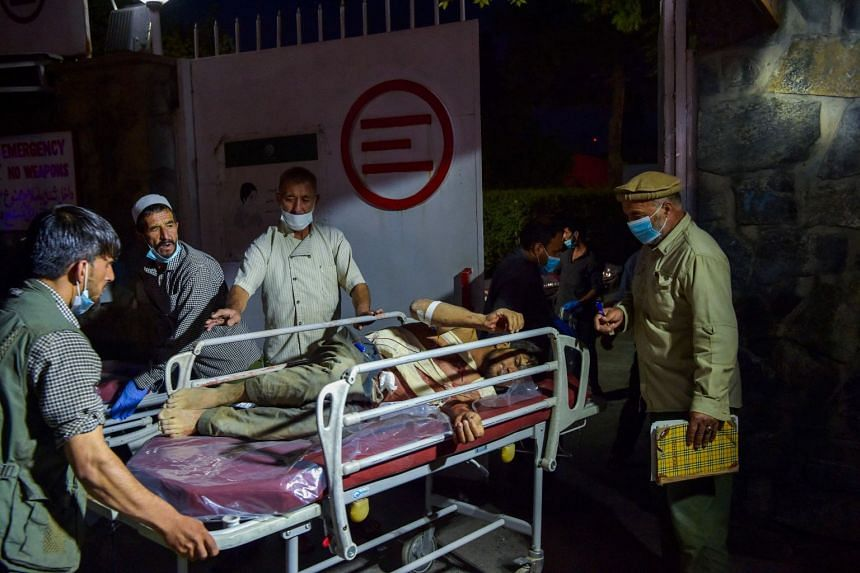 Medical and hospital staff bring an injured man on a stretcher for treatment after two powerful explosions outside the airport in Kabul.