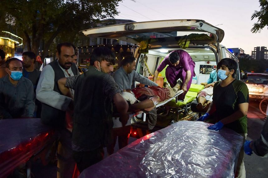 Volunteers and medical staff bring an injured man for treatment after two powerful explosions outside the airport in Kabul.