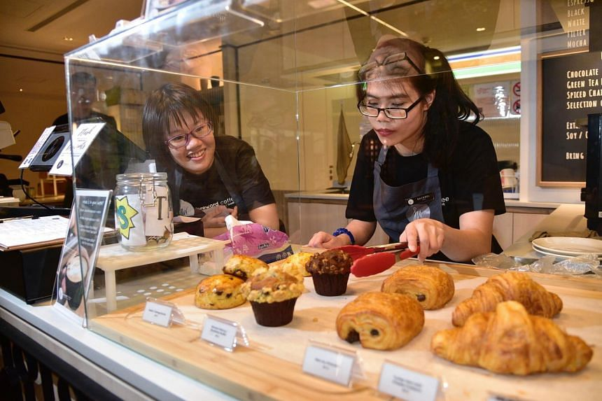 Ms Carmen Tan Yin Xin (left) and Ms Rachel Lum Yuan Ting are employees with special needs who work at Foreword Coffee, one of the Platinum award recipients this year.