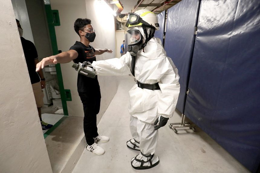 A SCDF officer demonstrating how those seeking shelter during a chemical attack must go through the decontamination process.