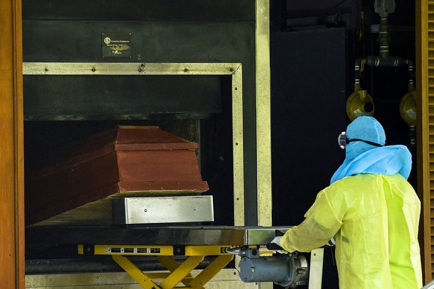A municipal worker places the coffin of an unclaimed Covid-19 victim inside a furnace at a crematorium in Sri Lanka on Aug 14, 2021.