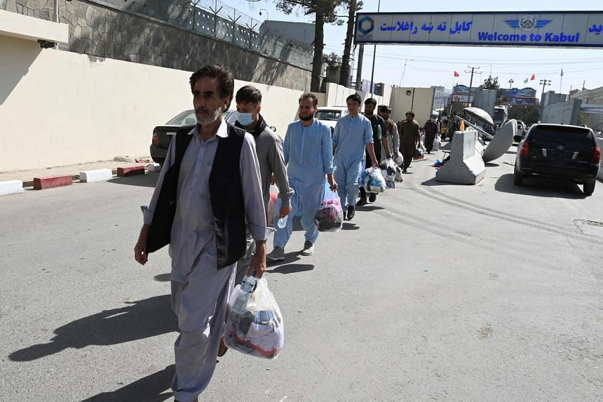Afghans hoping to leave the country walk to the main entrance gate of Kabul airport, on Aug 28, 2021.