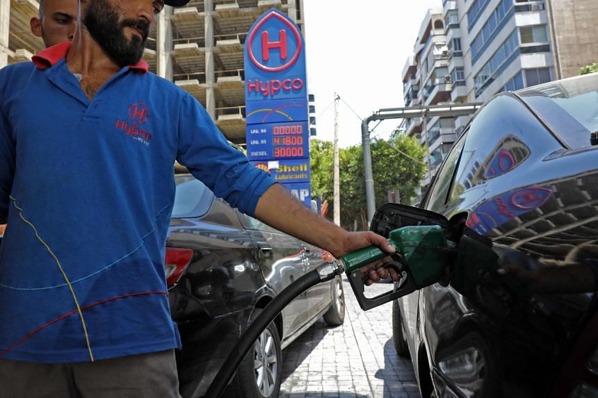 In this photo taken on June 11, 2021, an employee fills a car with fuel at a petrol station in Beirut.