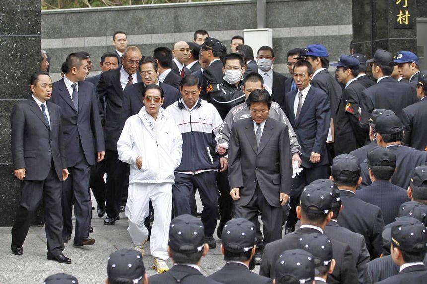 A photo from 2010 showing Kudo-kai head Satoru Nomura (in white) with Fukuoka police investigators during a raid of the gang's affiliate in Kitakyushu, Japan.