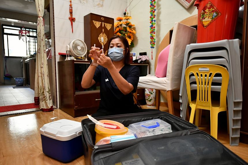 Nurse Masturina Mohamed Ariff, attached to home care provider Speedoc, preparing to vaccinate Ms Ang Kim Kee and her helper Lae Lae Win at their home on Aug 16, 2021.