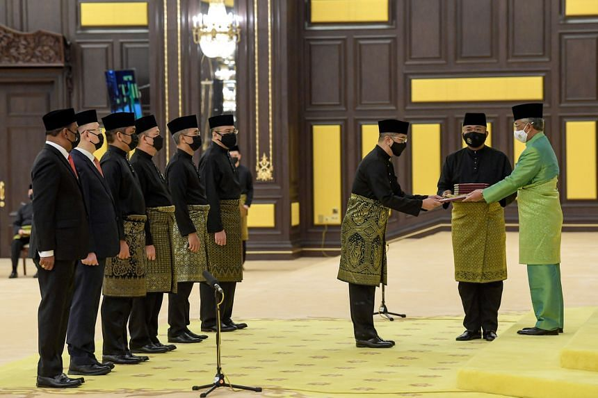 Sultan Abdullah Ahmad Shah (right) handing the instrument of appointment to Senior Minister of International Trade and Industry Mohamed Azmin Ali at the swearing-in ceremony on Aug 30, 2021.