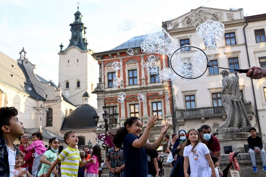 In this photo taken on Aug 13, 2021, Middle Eastern tourists play with soap bubbles in Lviv, Ukraine.