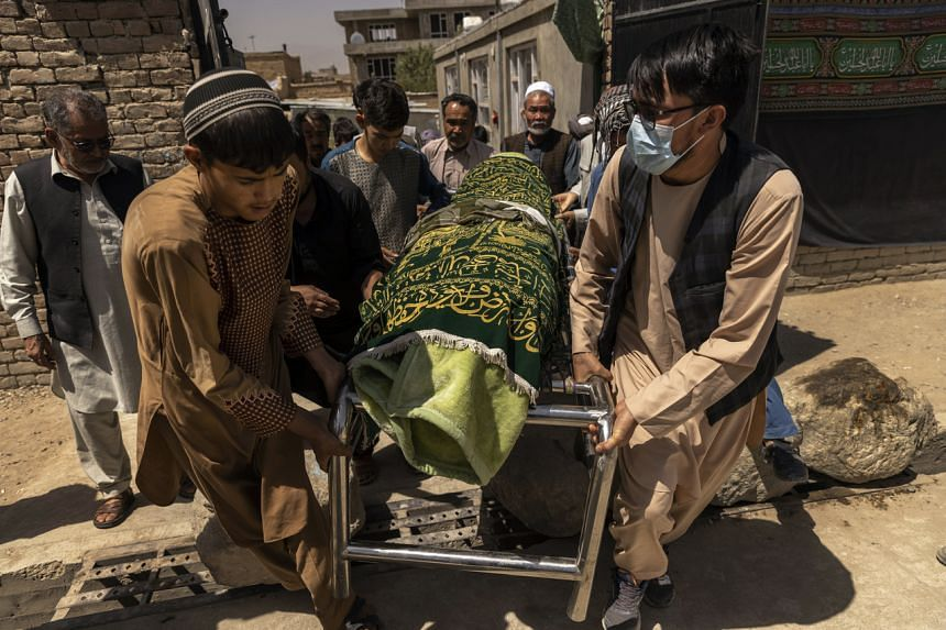 People transport the body of a person who was killed a day earlier in the suicide bombing attack for burial in the hills outside of Kabul on Aug 27, 2021.