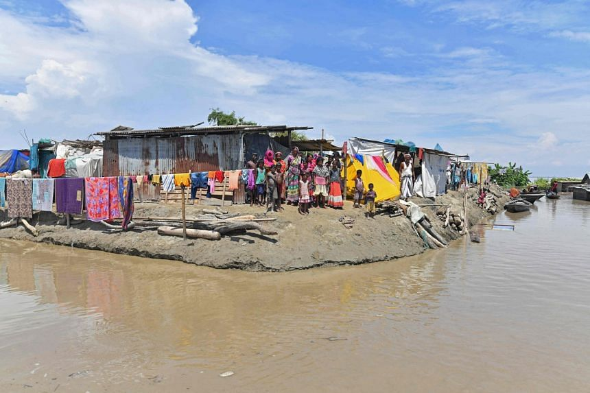 Villagers take shelter on higher grounds in a flood affected area of Morigaon district in Assam, on Aug 30, 2021.