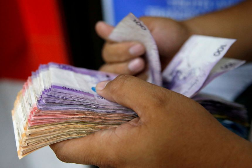 A man counts a wad of Philippine Peso bills at a money remittance center in Makati City, Philippines, on Sept 19, 2018.