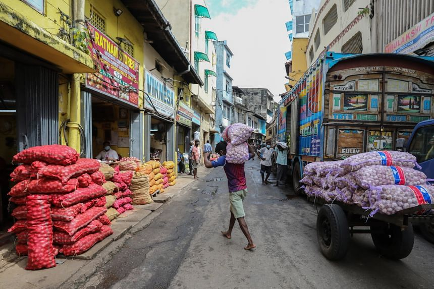 Workers unloading essential food products at a wholesale market in Colombo on Aug 30, 2021.