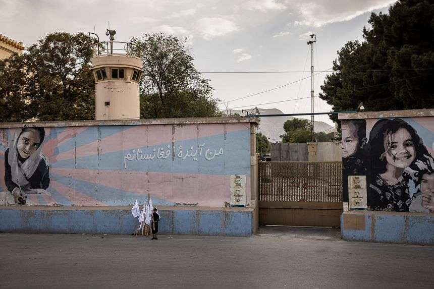 Taliban flags are sold outside the shuttered and abandoned US embassy in Kabul on Aug 22, 2021.
