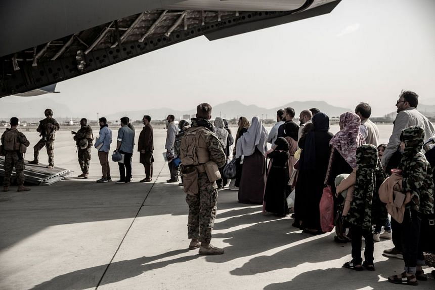 Evacuees wait to board a US plane at Hamid Karzai International Airport in Kabul, on Aug 30, 2021.