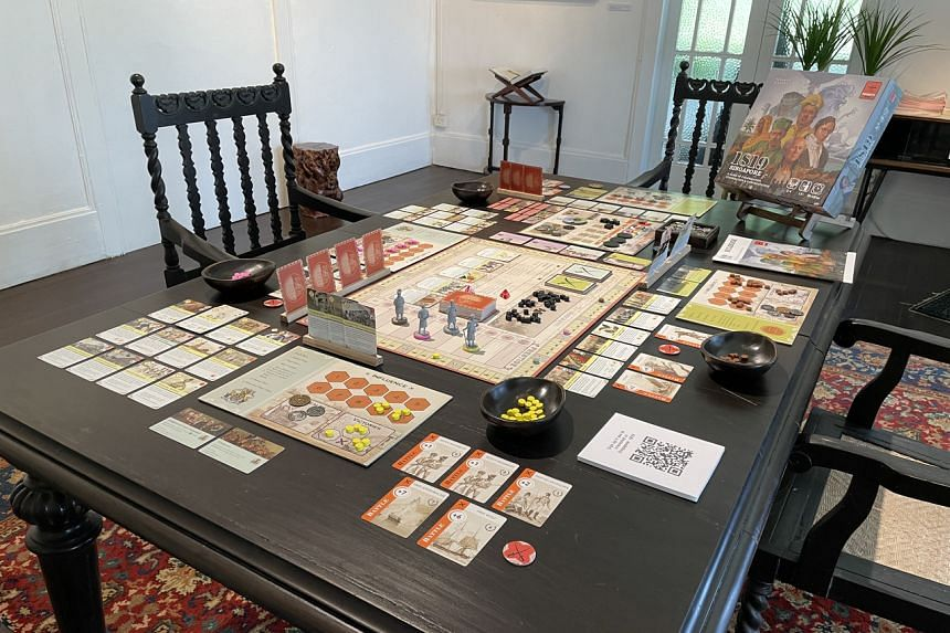 An amazingly detailed board game with tokens, figurines and playing cards is laid out on a table.