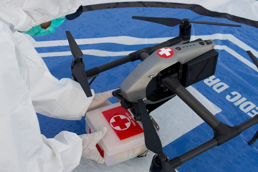 A medical worker on the deck of a passenger ship in Makassar, Indonesia, on Aug 27, 2021, taking a box of medical supplies that has been delivered by a drone.