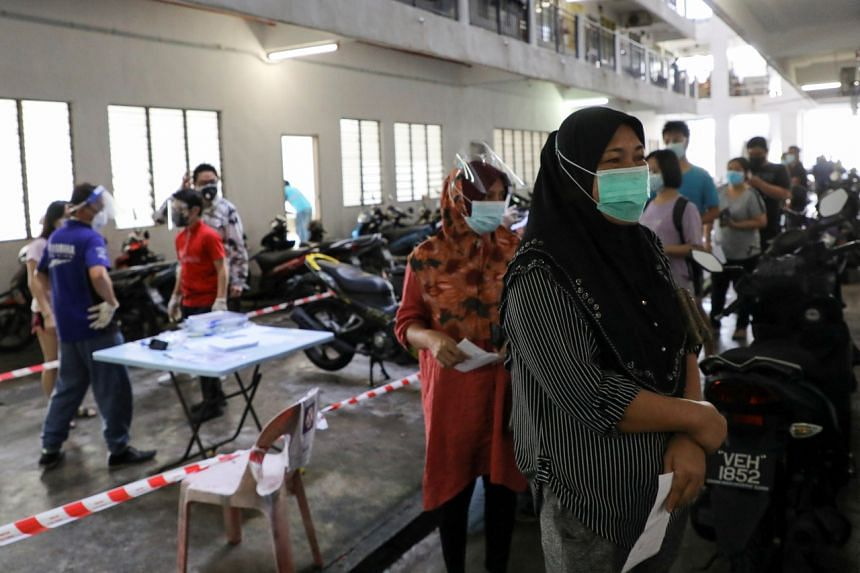 In a photo from July 12, 2021, people wait in line to be tested for Covid-19 in Seri Kembangan.