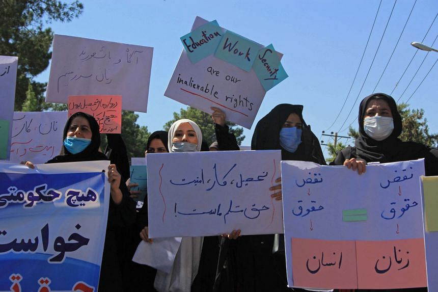 Afghan women hold placards as they take part in a protest in Herat on Sept 2, 2021.