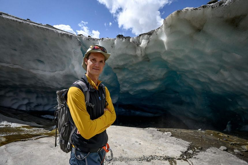 Swiss glaciologist Matthias Huss poses next to an ice cavity of the Aletsch Glacier on Aug 25, 2021.