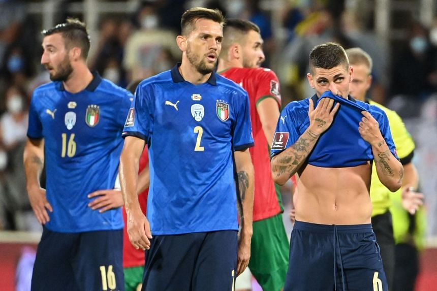Italy's midfielder Marco Verratti (right) and teammates react at the end of the match.