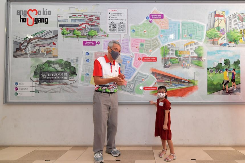Prime Minister Lee Hsien Loong and Raja Lana Adira Raja Mohammad Faizal in front of the mega jigsaw puzzle at Ci Yuan Community Club on Sept 4, 2021.