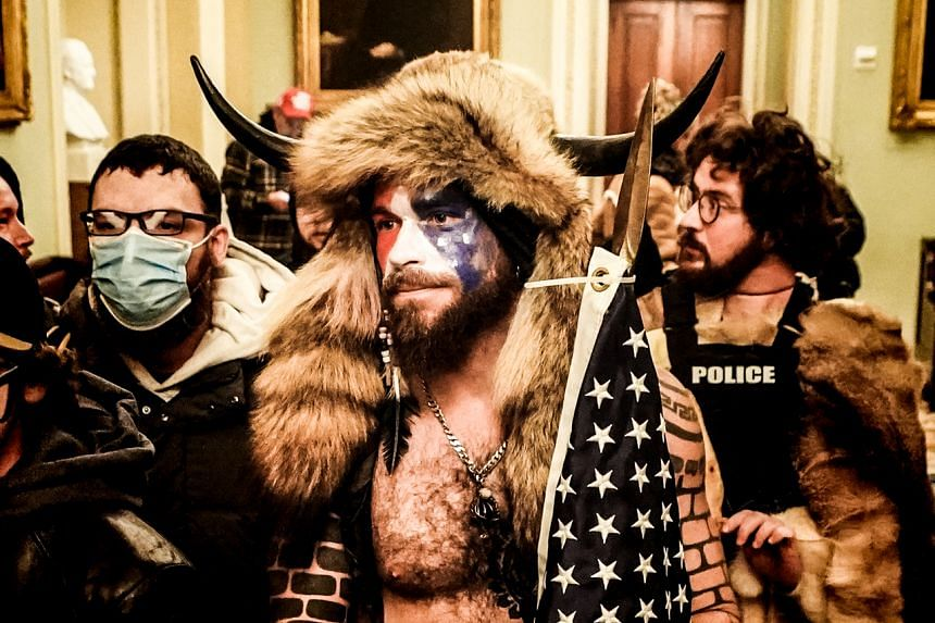 """A photo from Jan 6, 2021, showing Jacob Chansley, dubbed the """"QAnon Shaman"""", and other rioters inside the US Capitol in Washington. The man has been diagnosed with transient schizophrenia, bipolar disorder, depression and anxiety."""