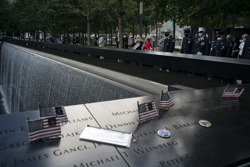 People stand at the 9/11 Memorial in New York, on Sept 11, 2020, the 19th anniversary of the Sept 11 terrorist attacks.