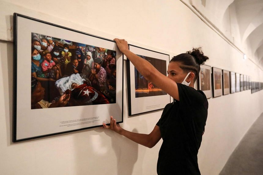 """A worker hanging photos for the exhibition """"Anonymous photographer in Myanmar"""" in Perpignan, France, on Aug 25, 2021."""