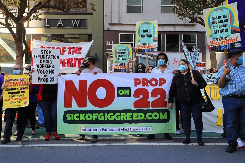 A file photo taken on Oct 15, 2020 shows people protesting against a ballot initiative that would allow Uber and Lyft to continue classifying drivers as independent contractors, in San Francisco.