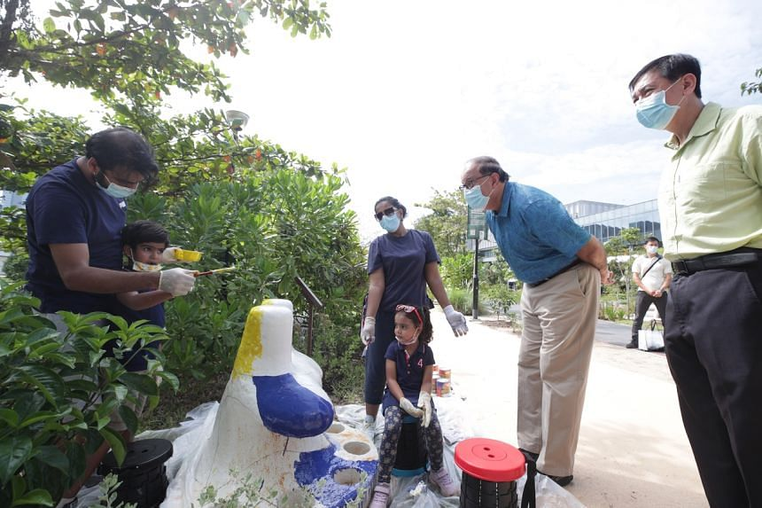 Transport Minister and West Coast GRC MP S. Iswaran speaking with a family engaged in a bollard-painting activity at Pasir Panjang Park on Sept 4, 2021.