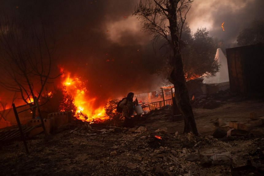 A migrant flees a fire at the the Moria migrant camp on the Greek island of Lesbos on Sept 9, 2020.