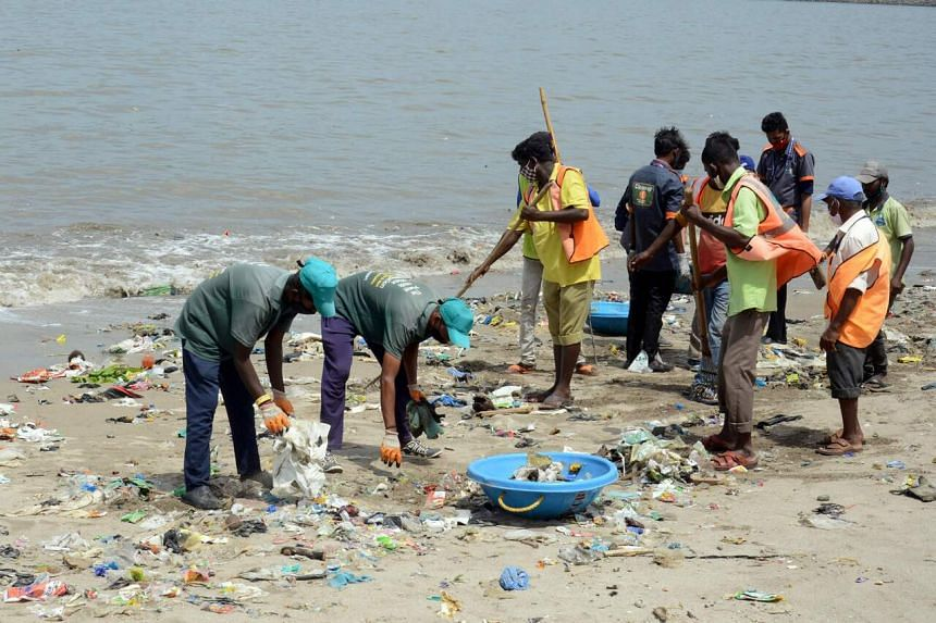 Municipal workers take part in a clean-up effort to remove waste and garbage at a beach in Mumbai on June 26, 2021.
