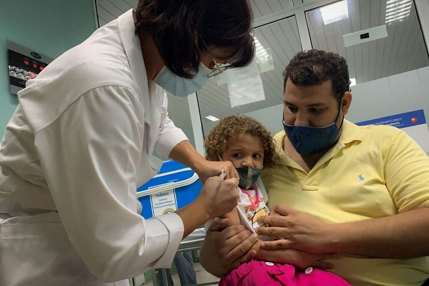 Pedro Montano holds his daughter Roxana, 3, as she is given the Cuban Covid-19 vaccine Soberana Plus as part of a study in Havana on Aug 24, 2021.