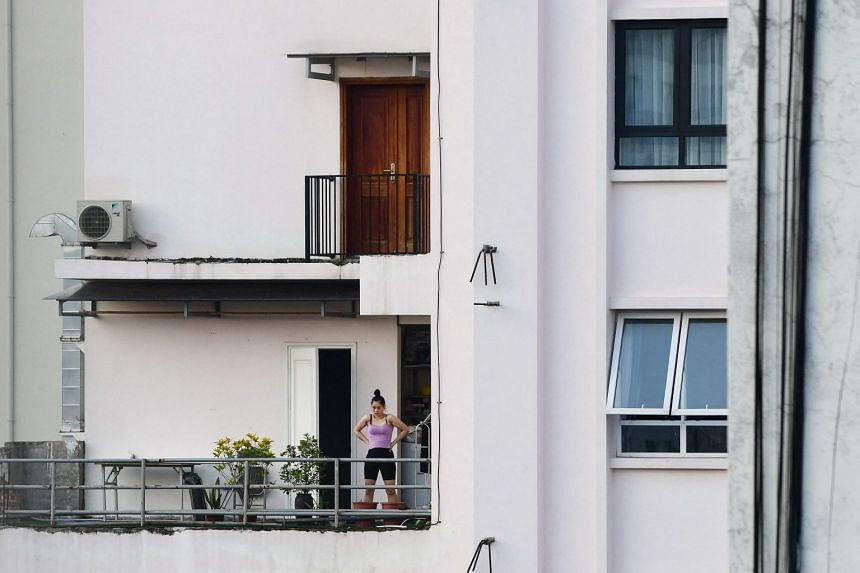 A woman exercising on the balcony of her home in Hanoi, during the government-imposed lockdown, on Sept 4, 2021.