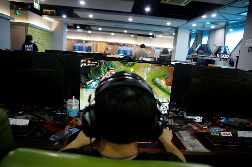 A man plays online game on a computer at an internet cafe in Beijing, on Aug 31, 2021.