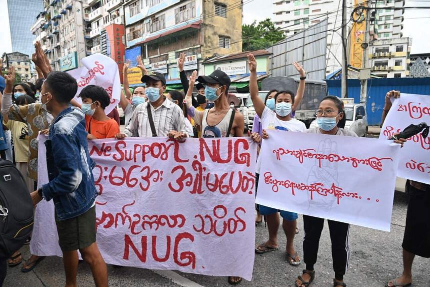 Protesters hold a banner supporting the National Unity Government during a demonstration in Yangon on July 11, 2021.